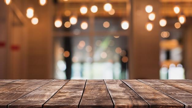 Lege houten tafelblad en wazig coffeeshop, café en restaurant interieur