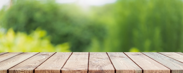 Lege houten tafelblad en wazig groene boom en groente in landbouwbedrijven. achtergrond.
