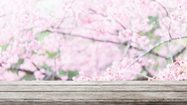 Lege houten tafelblad en wazig sakura bloem boom op tuin achtergrond.