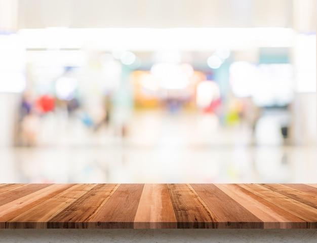 Lege houten tafelblad met boekh achtergrond van het onscherpte warenhuis