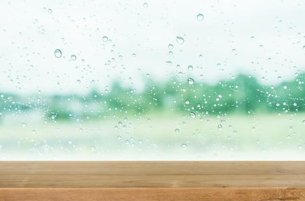 Lege houten tafelblad met glazen wand en waterdruppel achtergrond.