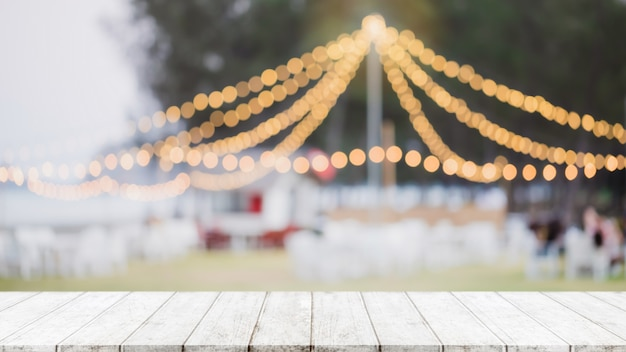 Lege houten tafelblad op abstracte wazig restaurant en nachtclub partij lichten achtergrond