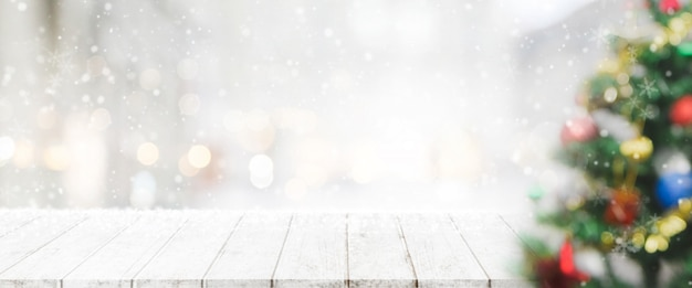 Lege houten tafelblad op onscherpte met bokeh kerstboom banner achtergrond met sneeuwval.