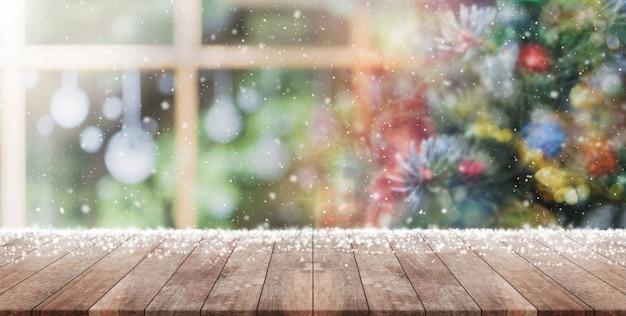 Lege houten tafelblad op vervagen met bokeh kerstboom en nieuwjaars decoratie achtergrond