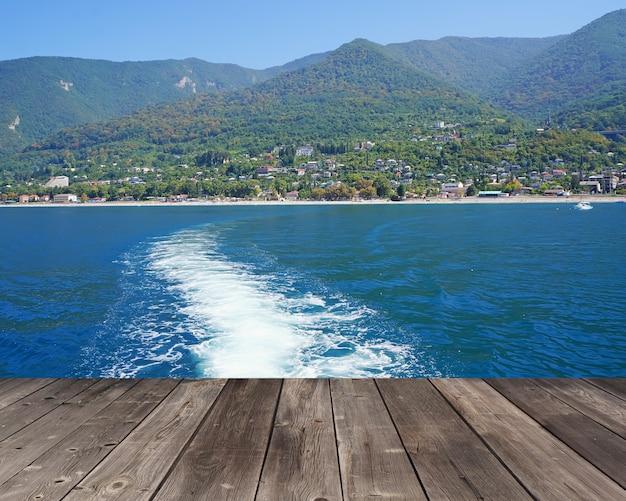 Lege houten vloeren tegen een schuimend spoor in de zee