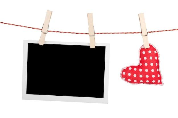 Lege instant foto en rood hart opknoping. geïsoleerd op witte achtergrond