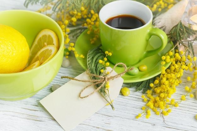 Lege kaart met mimosa, citroen en koffie op lichte houten tafel