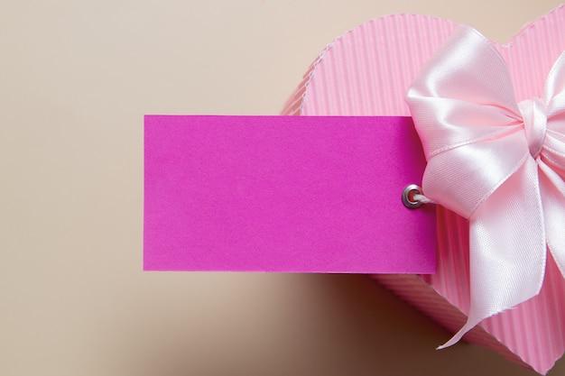 Lege kaart met roze hartvormige geschenkdoos en boog