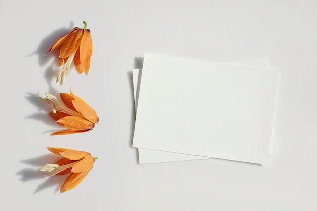 Lege kaart of nota en oranje leliesbloemen met harde schaduwen