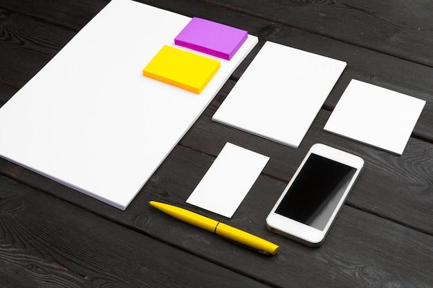 Lege kantoorbehoeften die op zwart hout wordt geplaatst. papier, visitekaartjes, boekjes, vellen, enz