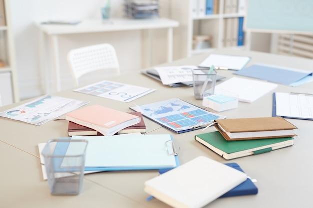 Lege kantoorwerkplek met documenten en grafieken op wit bureau