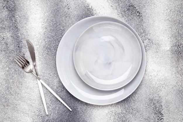 Lege keramische plaat en ongebruikt mes met vork, bestek op grijze tafel, serveerconcept. platliggend ontwerp. restaurant menu. wenskaart, lay-out, mockup met kopieerruimte. bovenaanzicht. sjabloon.