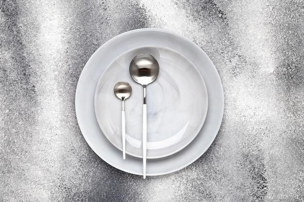 Lege keramische plaat en ongebruikte theelepel met eetlepel, bestek op een grijze tafel, serveerconcept. platliggend ontwerp. restaurant menu. wenskaart, lay-out, mockup met kopieerruimte. bovenaanzicht. sjabloon.