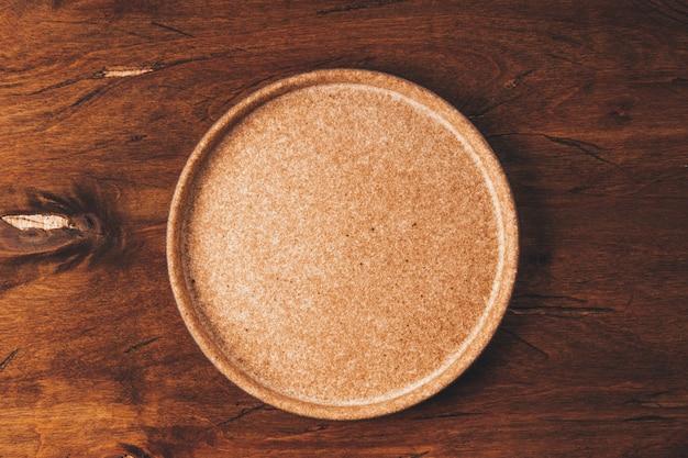 Lege keramische plaat op bruin houten achtergrond bovenaanzicht. hoge kwaliteit foto