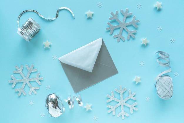 Lege kerstkaart en envelop met zilveren versieringen op blauwe ondergrond, bovenaanzicht. vakantie hipster