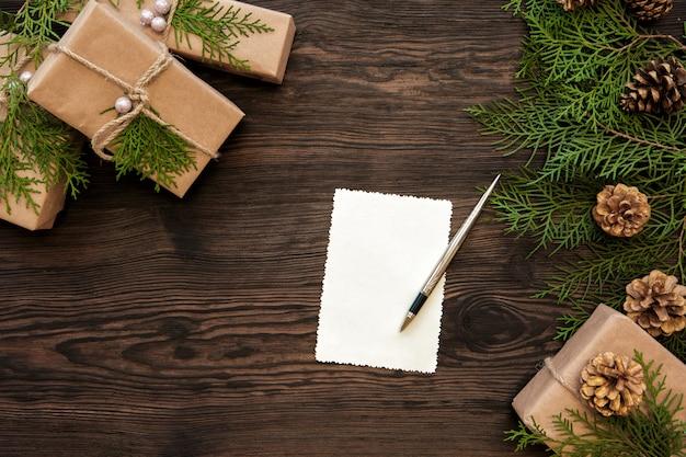 Lege kerstkaart, geschenkdozen, tak en dennenappels op hout