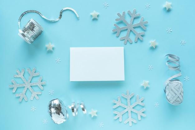 Lege kerstkaart met zilveren kerstversiering op blauwe ondergrond, bovenaanzicht. vakantie hipster