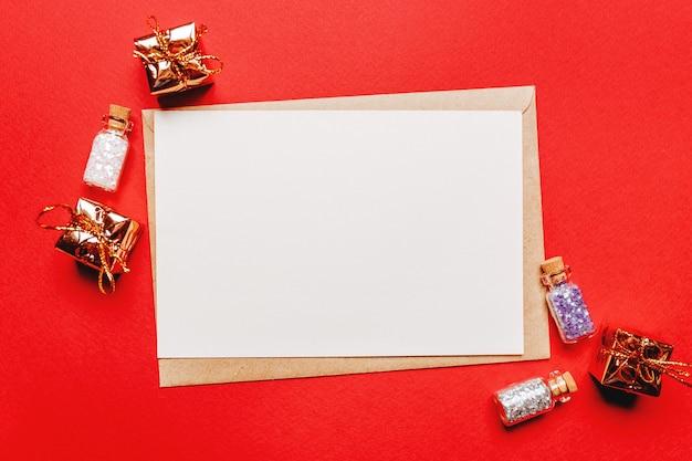 Lege kerstmissota met gift en stuk speelgoed op geïsoleerd rood.
