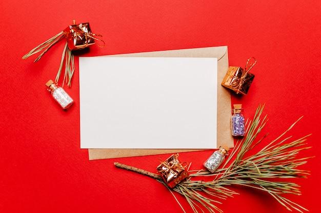 Lege kerstnota met cadeau, spartak en speelgoed op rode geïsoleerde achtergrond. nieuwjaarsconcept