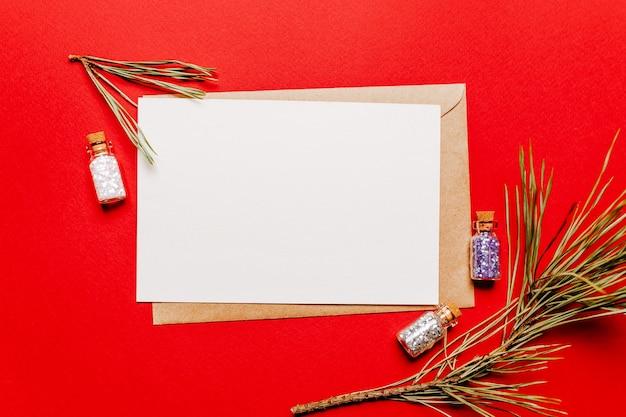 Lege kerstnota met spartak en sparren speelgoed op rode geïsoleerde achtergrond. nieuwjaarsconcept