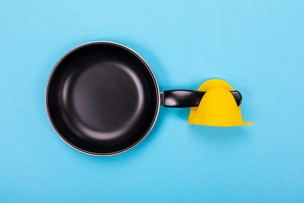 Lege keukenpan met ovenwant die op blauw wordt geïsoleerd