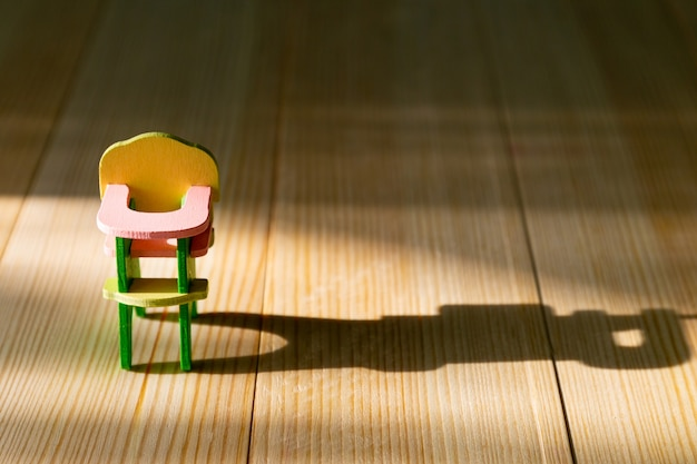 Lege kinderstoel op houten achtergrond