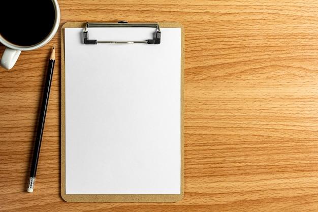 Lege kladblok en een potlood op houten bureau.