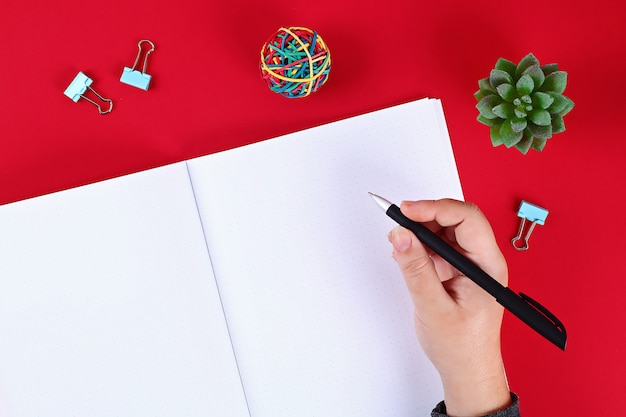 Lege kladblok op rode tafel, plant, pen. bovenaanzicht, platliggend. mockup, kopieer ruimte.