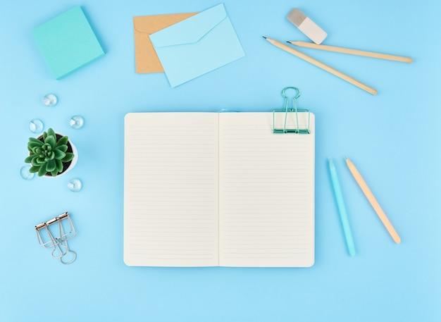 Lege kladblok-pagina voor tekst op blauwe office-bureaublad. bovenaanzicht van moderne heldere tafel-laptop,