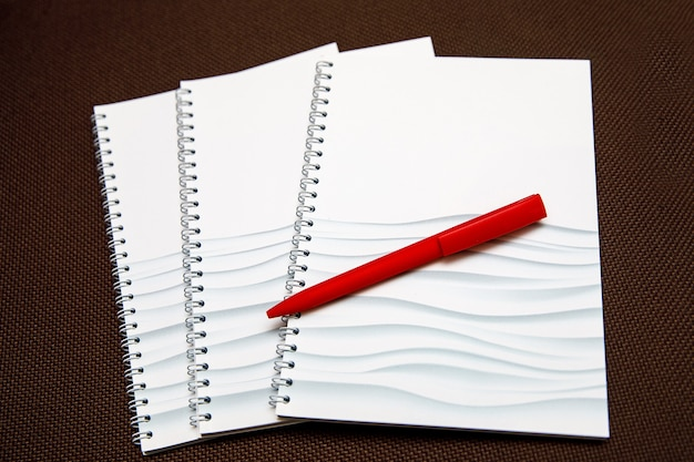 Lege kladblok voor tekst met rode pen op houten achtergrond.