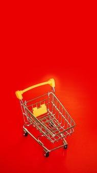 Lege kleine gele winkelwagen op rode achtergrond. kopieer ruimte, plaats voor tekst. concept verkoop. verticale foto