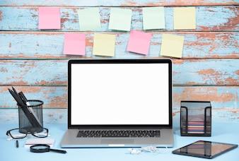 Lege kleurrijke zelfklevende notities tegen houten muur met kantoorbenodigdheden en laptop