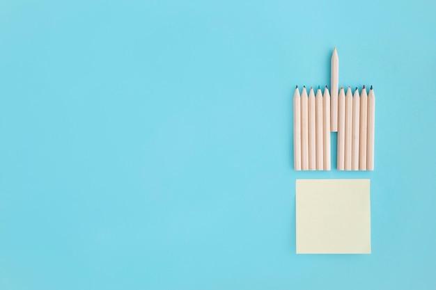 Lege kleverige nota met rijen van kleurpotlood over blauwe achtergrond
