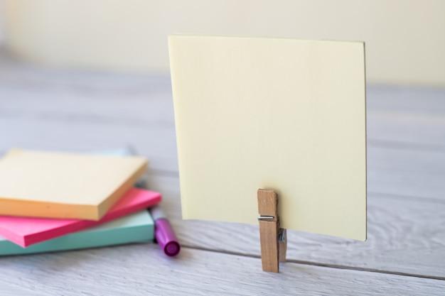 Lege kleverige nota met wasclip stapel kleurrijke papieren pen geplaatst op een leeg stuk tafel