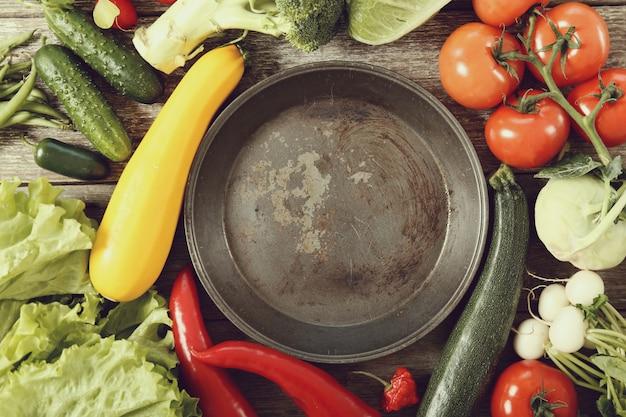 Lege koekenpan met groenten rond, bovenaanzicht