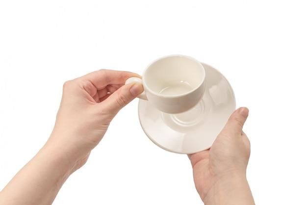 Lege koffiekop in vrouwenhand die op wit wordt geïsoleerd.