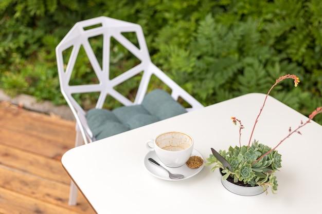 Lege koffiekop op een witte achtergrond. terras met een tafel in een café, vetplanten in pot buiten, ochtendtijd