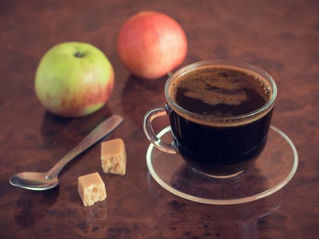 Lege koffiekopje met lepel en twee appels op de tafel.