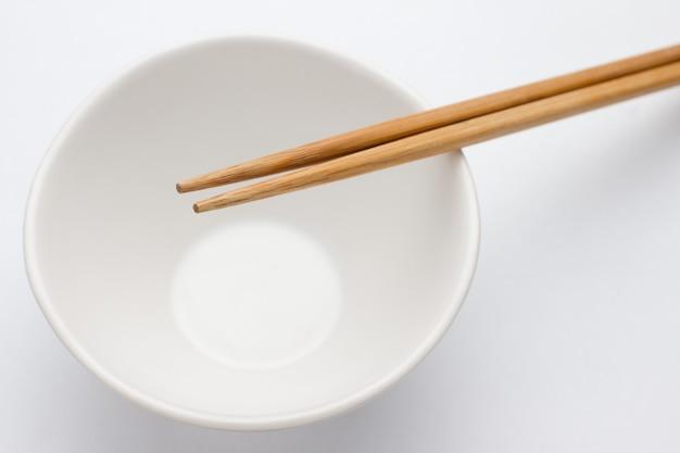 Lege kom en eetstokje op wit wordt geïsoleerd
