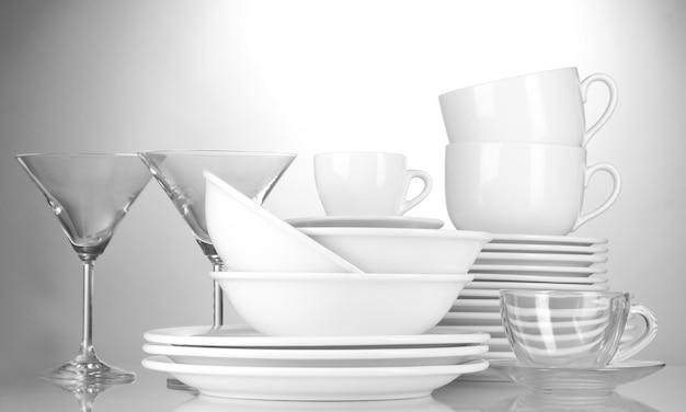 Lege kommen, borden, kopjes en glazen op grijs
