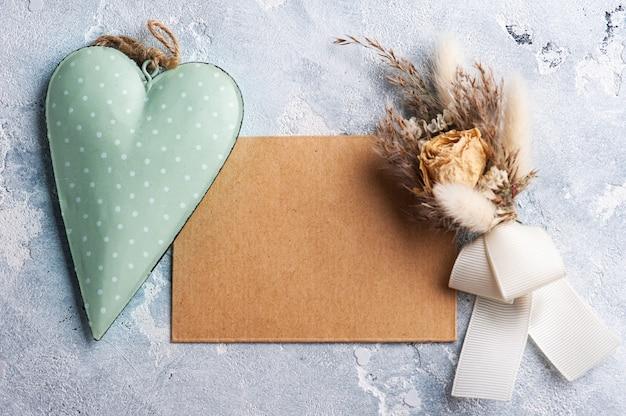 Lege kraftpapier-envelop met boeket van droge bloemen en groen hart. bruiloft mock up op grijze tafel
