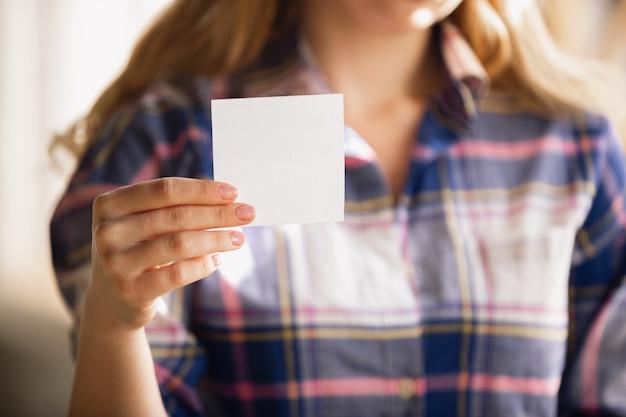 Lege lakens vasthouden. close up van blanke vrouwelijke handen, werkzaam in kantoor. concept van zaken, financiën, baan, online winkelen of verkopen. kopieerruimte. onderwijs, communicatie freelance.