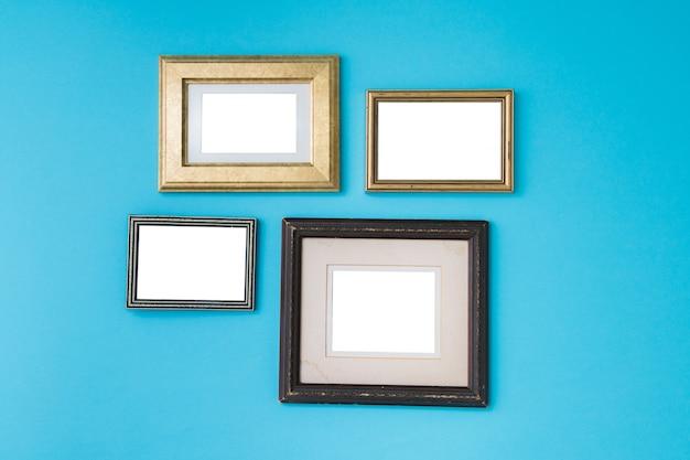 Lege lege gouden en houten frames op blauwe achtergrond.