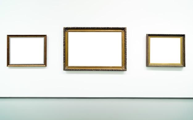 Lege lege gouden schilderij frames aan de muur op tentoonstelling.