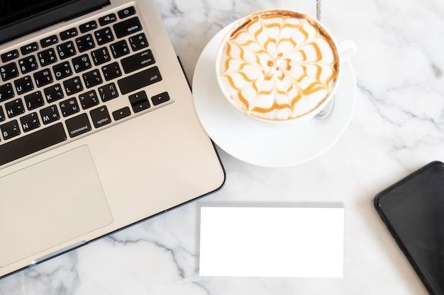 Lege lege visitekaartjeslaptop en kop van koffie op het bureau.