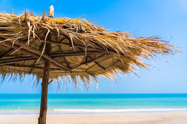 Lege ligstoel lounge met paraplu rond op strand zee oceaan blauwe hemel voor vakantiereizen vakantie
