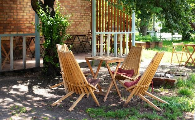 Lege ligstoelen en tafel op veranda van huis in bos. tuinmeubilair voor vrije tijd in de natuur.