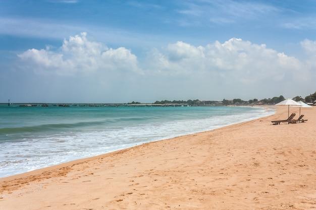 Lege ligstoelen onder de parasol op het strand
