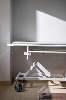 Lege medische kar op wielen die tegen een witte muur en raam in de ziekenhuiskamer of in de gang van hedendaagse covid-klinieken staan