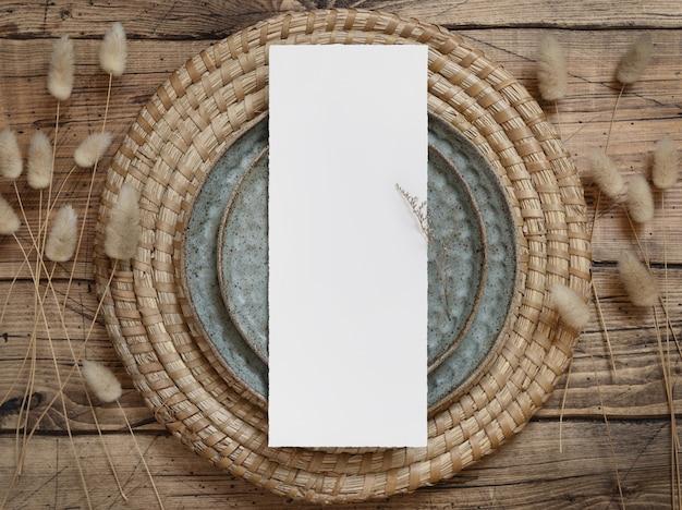 Lege menukaart op plaat op houten tafel met boheemse decoraties en gedroogde planten, bovenaanzicht. boho trouwkaart mockup